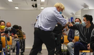 Boris Johnson meets patients during a visit to the vaccination centre