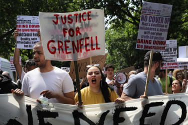 LONDON, ENGLAND - JUNE 21:Protesters hold signs calling for justice for the victims of the Grenfell Disaster and shout slogans as they march towards Westminster during an anti-government prot