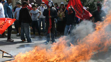 Demonstrators set on fire campaign posters of Juan Orlando Hernandez in front of the US embassy