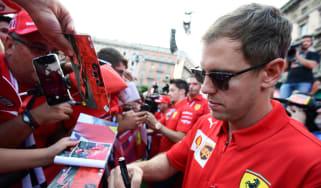 Sebastian Vettel signs autographs at a Ferrari event in Milan on 4 September