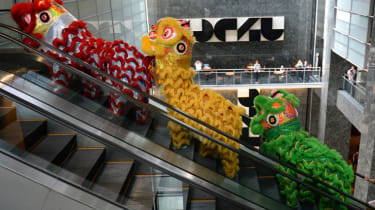 Performers wearing lion dance costumes ride an escalator as they make their way to the Philippine stock exchange for Lunar New Year of the Sheep celebrations in Manila on February 18, 2015. T