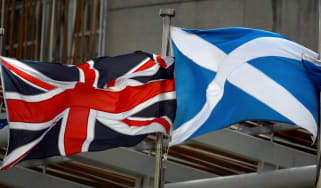 A Scottish Saltire and Union Jack flags flutter outside the Scottish Parliament