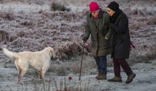 Couple walk with their dog in a freezing morning in London