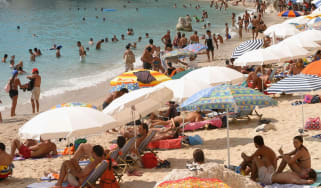 Tourists visit a Greek beach