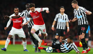 Arsenal midfielder Mesut Ozil takes on Newcastle's Mohamed Diame, Deandre Yedlin and Florian Lejeune