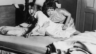 1973, American actor Ellen Burstyn restrains American actor Linda Blair on a bed in a still from the film 'The Exorcist', directed by William Friedkin. (Photo by Warner Bros./Getty Images)