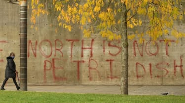 A pedestrian wearing a face-mask walks past graffiti declaring that 'the north is not a petri dish'.