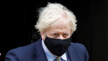 Boris Johnson leaves Downing Street wearing a black face mask.