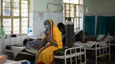 A relative sits with her family member in a hospital in Rajasthan, India