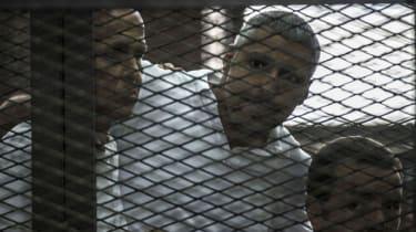Journalists Peter Greste, Mohamed Fadel Fahmy, and Egyptian Baher Mohamed listen to the court's verdict