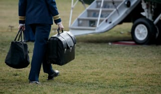 A military aide carries the 'nuclear football', which travels with the president at all times