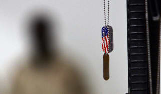 A US dogtag hangs next to an M16 rife