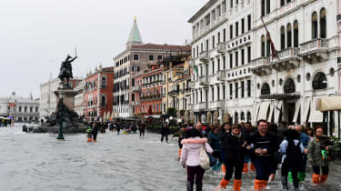 People walk in the flooded Riva degli Schiavoni during a high-water (Acqua Alta) alert in Venice on October 29, 2018. - The flooding, caused by a convergence of high tides and a strong Sirocc