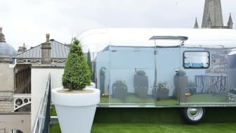 A silver airstream caravan on top of a roof