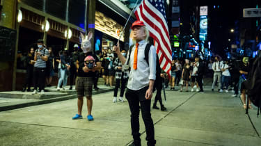 A demonstrator wears a Donald Trump mask while holding a U.S. flag in the Lan Kwai Fong area of Hong Kong, China, on Thursday, Oct. 31, 2019. Efforts by Hong Kongs authorities to quell the pr
