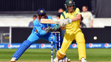 Australia's Adam Voges (R) plays a shot as India's captain wicketkeeper Mahendra Singh Dhoni looks on during the warm-up cricket match ahead of the 2013 ICC Champions Trophy between India and
