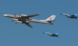 Russian startegic bomber TU-95 surrounded by MiG-29 flies over Monino airfield, some 40 km from Moscow, during an air show marking 95th anniversary of foundation of Russian Air Forces, 11 Aug
