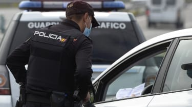 A spanish police officer controls cars at a traffic checkpoint