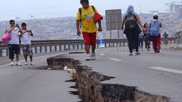 People walk along a cracked road in Iquique, northern Chile, on April 2, 2014 a day after a powerful 8.2-magnitude earthquake hit off Chile's Pacific coast. An 8.2-magnitude earthquake hit Ch