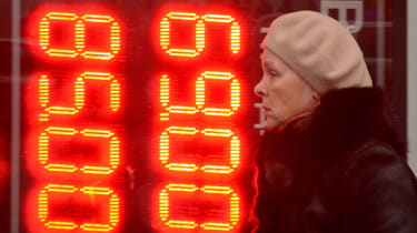 A woman walks past a board listing foreign currency rates outside an exchange office in central Moscow