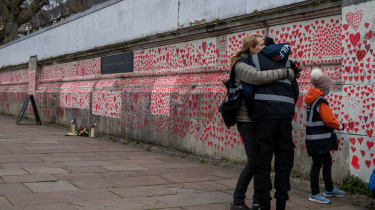 A woman hugs her son as they draw hearts on the Covid-19 Memorial Wall which is nearing completion opposite Parliament