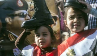 A portrait of Abdel Fattah al-Sisi behind two Egyptian girls