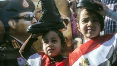 A portrait of Abdel Fattah al-Sisi behind two Egyptian girls