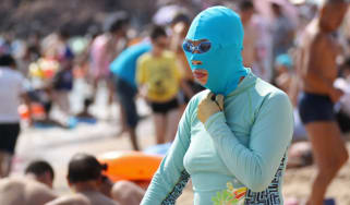 A Chinese beachgoer wearing a bathing suit and head mask