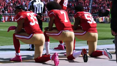 Eric Reid, Colin Kaepernick and Eli Harold kneel for the national anthem