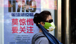 A woman wears a face mask as she walks past a poster showing how to avoid the H7N9 avian influenza virus, by a road in Beijing on April 24, 2013. International experts probing China's H7N9 bi