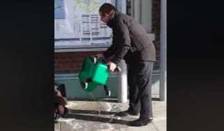Rail staff pour dirty water onto a homeless man
