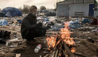 A refugee keeps warm at the Jungle refugee camp in Calais