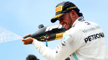 Mercedes driver Lewis Hamilton celebrates on the podium after his win at the French GP