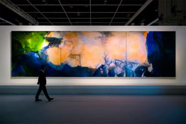Man walking past and looking at large triptych painting