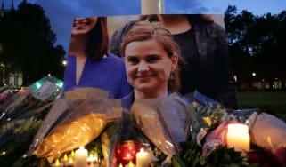 Floral tributes and candles are placed by a picture of Labour MP Jo Cox