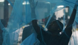 A worker inspects a mosquito net in Arusha, Tanzania