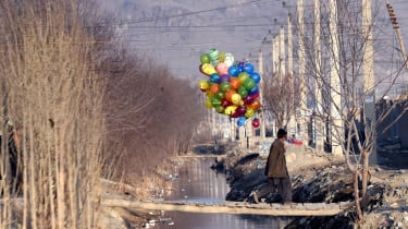 An Afghan boy carries balloons as he crosses a temporary wooden bridge in Kabul on February 4, 2015. Afghanistan's economy has improved significantly since the fall of the Taliban regime in 2