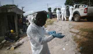 MONROVIA, LIBERIA - AUGUST 14:Aburial team prepares to collect the dead body of a woman suspected of dying of the Ebola virus on August 14, 2014 in Monrovia, Liberia. Teams of undertakers wea
