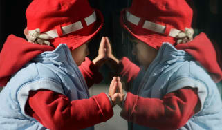A child looks at his reflection in a window in Beijing