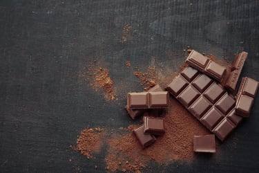 A chocolate bar broken into pieces with scattered chocolate dust.