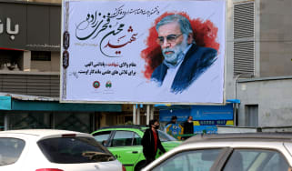 Vehicles drive by a billboard in honour of slain nuclear scientist Mohsen Fakhrizadeh in the Iranian capital Tehran, on November 30, 2020. - Iran laid to rest a nuclear scientist in a funeral