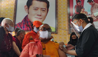A Buddhist monk receives a vaccine below an image of King Jigme Khesar Namgyel Wangchuck