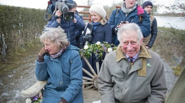 MUCHELNEY, UNITED KINGDOM - FEBRUARY 04:Prince Charles, Prince of Wales smiles as he is transported on a tractor trailer through the flood hit village of Muchelney to Thorney Moor Farm on Feb