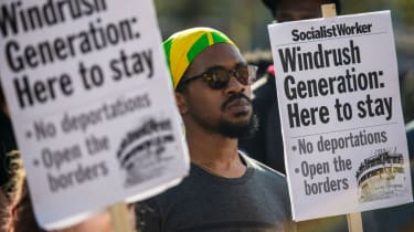 Demonstrators hold placards during a protest in support of the Windrush generation in Windrush Square, Brixton