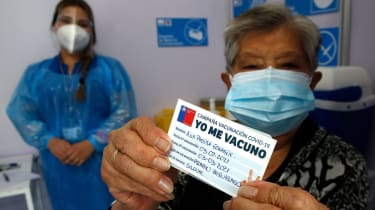 A Chilean woman shows her vaccination card