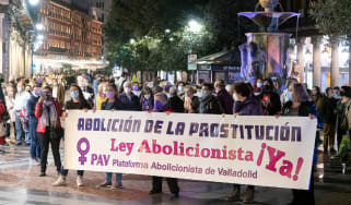 Women hold a banner calling for a law to criminalise prostitution