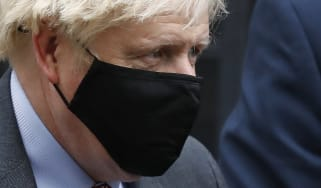 Boris Johnson leaves Downing Street wearing a face mask.