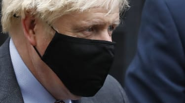 Boris Johnson leaves Downing Street wearing a face mask.