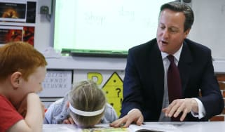 Britain's Prime Minister David Cameron reads a book to Lucy Howarth, 6, (L), and Will Spibey, 5, during a visit to Sacred Heart RC primary school in Westhoughton near Bolton on April 8, 2015.
