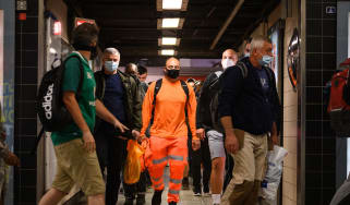 Commuters wear face masks as they pass through Vauxhall underground station, London.